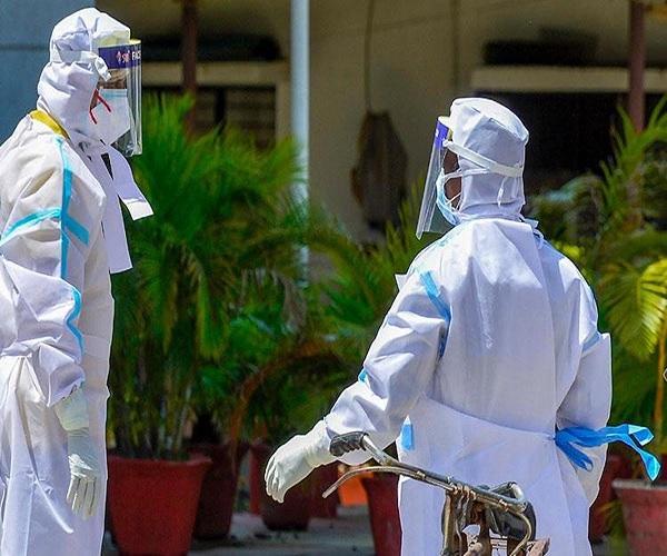 PPE किट पहने पत्रकार और फोटोग्राफर-